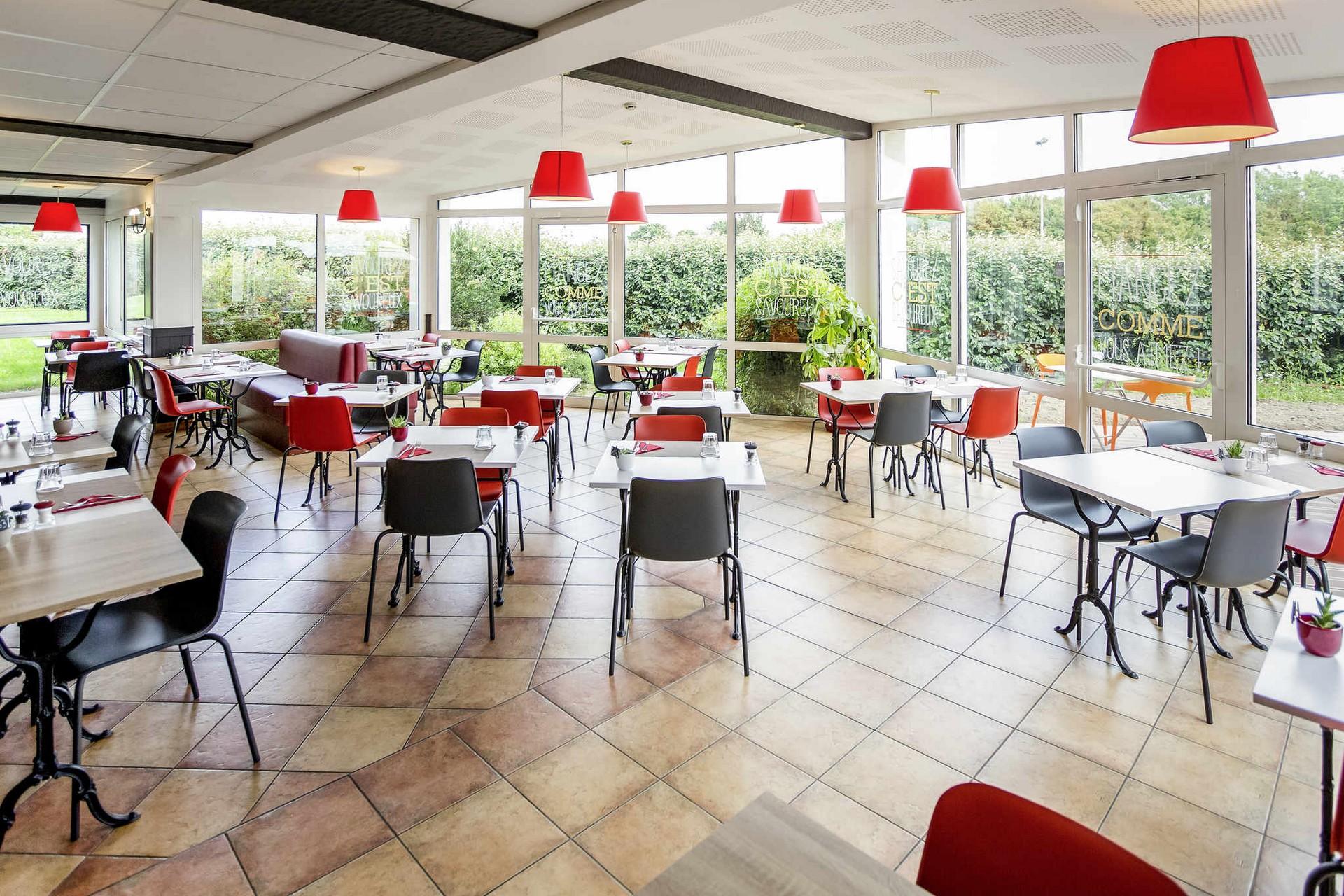 Une salle de restaurant lumineuse et moderne à l'Ibis Cherbourg La Glacerie